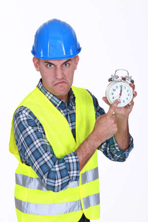 Angry builder pointing at alarm clock photo