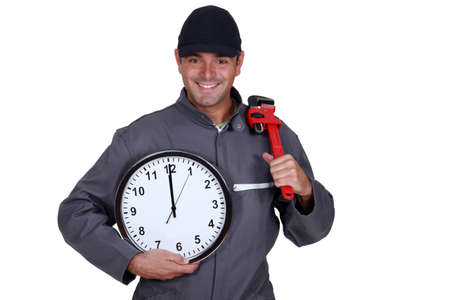 Handyman holding a pipe wrench and a clock photo