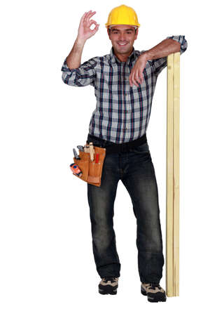 Tradesman leaning on planks of wood and giving the a-ok sign