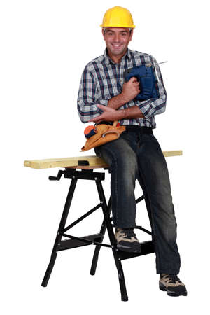 carpenter's bench: Tradesman holding a jigsaw