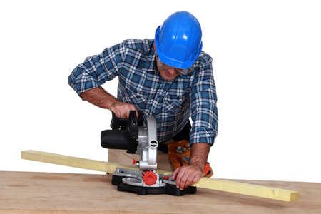 miter: Woodworker using miter saw