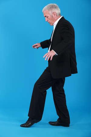 firmeza: Un hombre de negocios maduro caminando sobre una línea invisible.