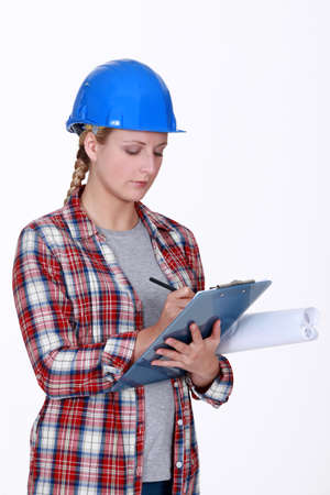 office notes: Female construction worker writing on clip-board