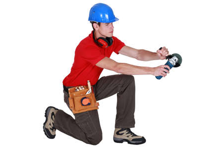 kneeling man: craftsman holding an electric saw