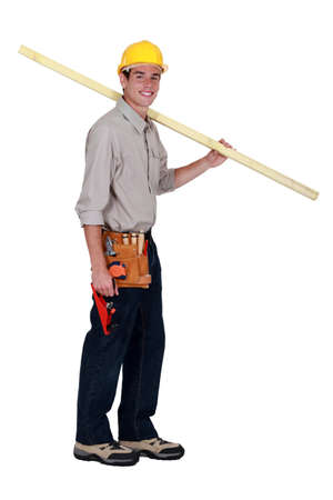 young carpenter in studio carrying plank over his shoulder photo