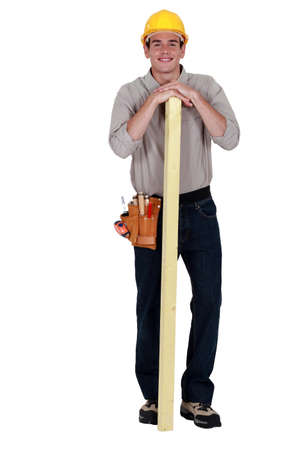 forest products: Carpenter stood with plank of wood Stock Photo
