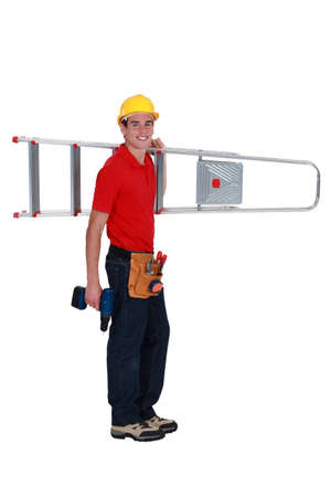 Young tradesman carrying a stepladder photo