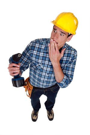 perturbed: craftsman holding a drill and looking upset