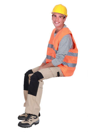 Young tradesman sitting on an invisible block