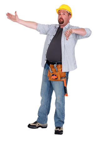 disapprove: Tradesman pointing to an object and giving the thumbs down