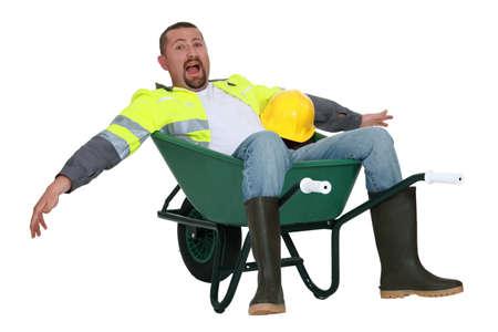 Goofy tradesman sitting in a wheelbarrow