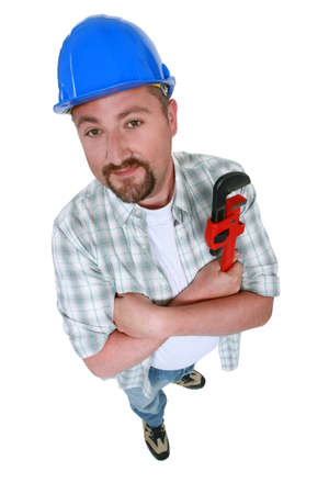 high angle shot: plumber with folded arms holding spanner Stock Photo