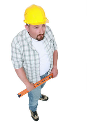adjusted: Grumpy manual worker holding spirit-level Stock Photo