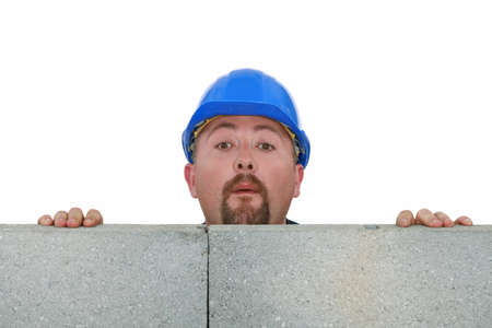 watch over: Builder peering over wall