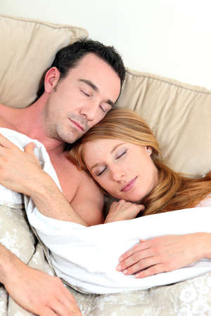 young couple sleeping in bed photo