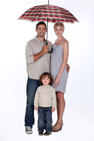 Young family standing underneath an open umbrella photo