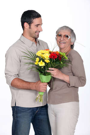Son giving mother flowers photo
