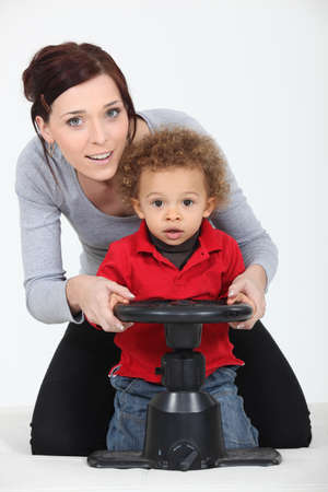 a mother and her son playing with a steering wheel photo