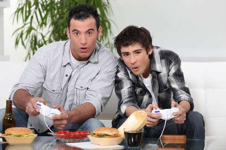 jugando videojuegos: Padre e hijo que juegan juegos de video Foto de archivo