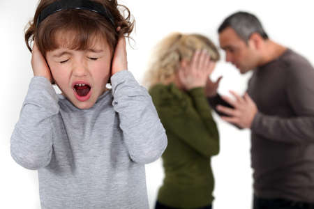 people arguing: Young child trying to block out her parents argument
