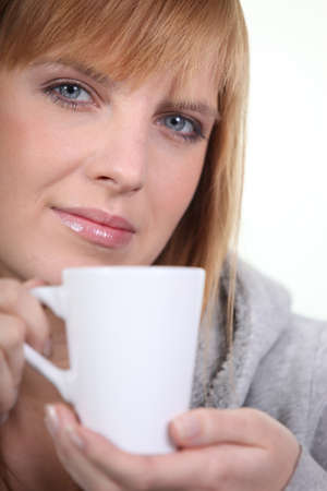 white headed: red-haired woman holding mug Stock Photo