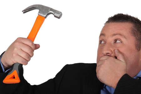 unplanned: Man in suit holding hammer