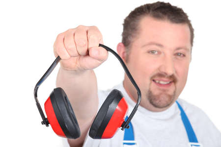 closely cropped: worker in blue overalls holding out ear protection Stock Photo