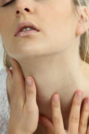 wisps: Woman touching her neck Stock Photo