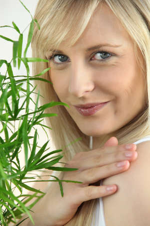Cute blond woman near a plant photo
