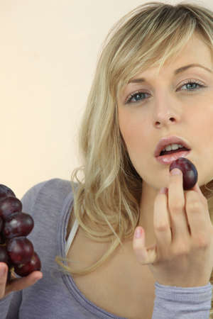Young fair-haired woman eating grapes photo