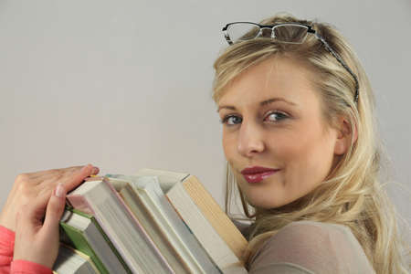 Young woman carrying a pile of books photo