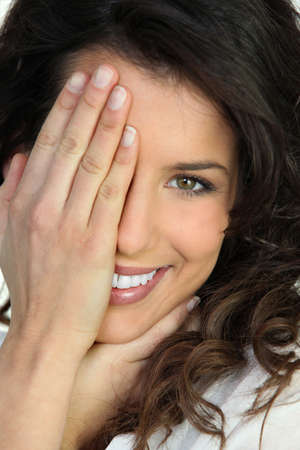 bashful: Woman covering an eye with her hand