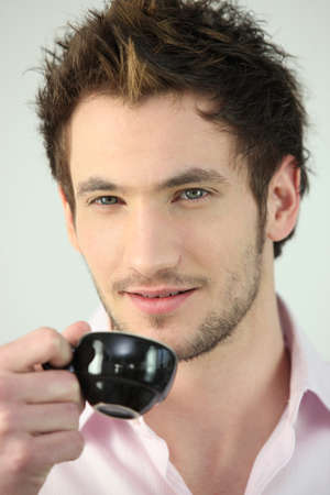expresso: Young man drinking a cup of expresso