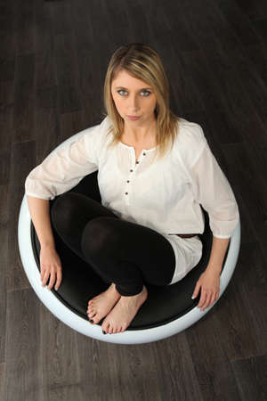 designer chair: Woman sat barefoot in designer chair Stock Photo