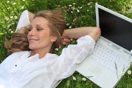 lounging: Pretty lady lounging in the grass next to laptop computer Stock Photo