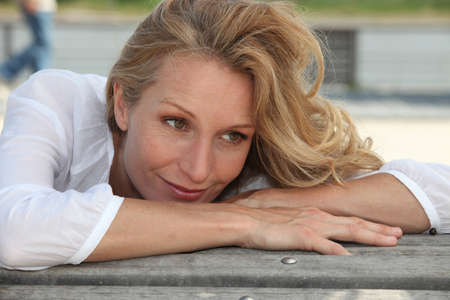 causcasian: Woman with long blonde hair leaning on a bench