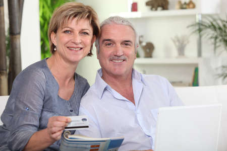 all smiles: middle-aged couple all smiles with computer sharing moment