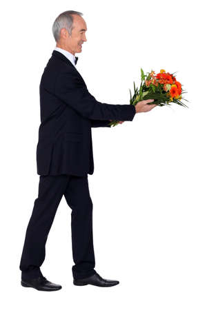 lowers: Man dressed in tuxedo holding bunch of lowers Stock Photo