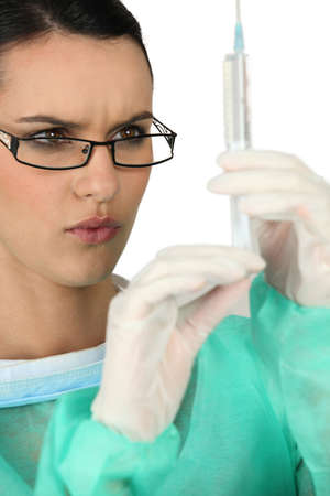 frown: A medical professional preparing a needle Stock Photo
