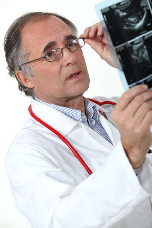scrutinise: Medical doctor examining an x-ray