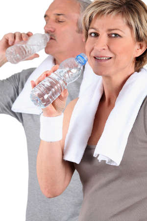 55 60: couple senior drinking water after training