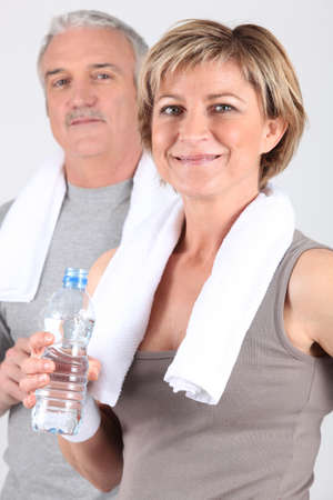 man gym: Mature couple drinking water after a workout