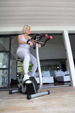 Senior woman on an exercise bike photo