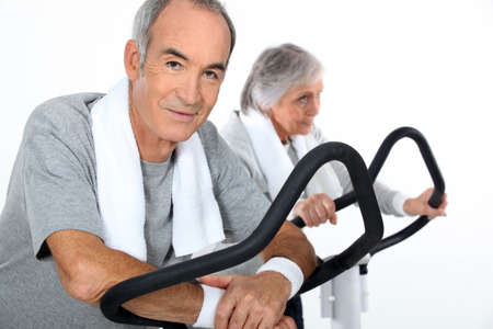 verve: senior couple doing cardio machine Stock Photo