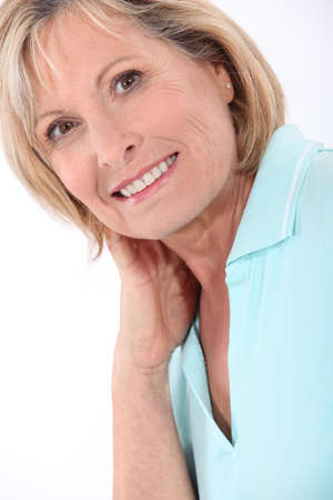affability: mature blonde woman wearing a turquoise polo shirt having a large smile Stock Photo
