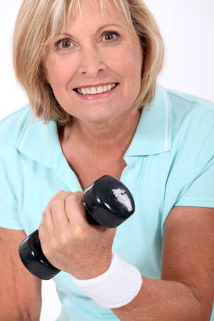50 55 years: Woman lifting a dumbbell Stock Photo