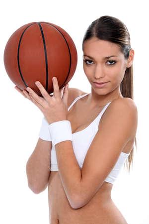 Mujer que hace la gimnasia con pelota de baloncesto photo
