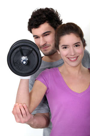 all smiles: coach and young woman all smiles lifting weight