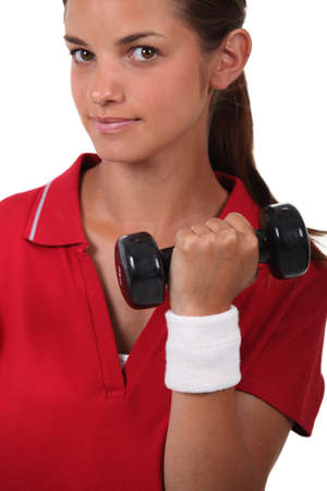 Young woman lifting weights photo