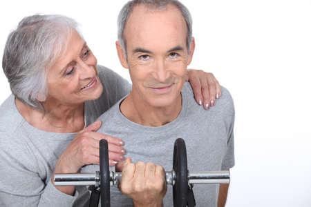 veneration: Woman admiring a man lifting a dumbell Stock Photo